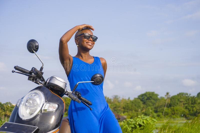 Young beautiful and happy african american black woman posing cool on scooter motorbike at green field tropical landscape. In adventure trip and summer holidays royalty free stock images