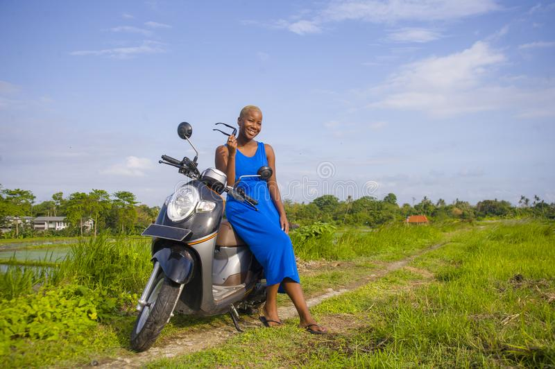 Young beautiful and happy african american black woman posing cool on scooter motorbike at green field tropical landscape. In adventure trip and summer holidays stock photos