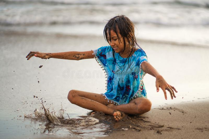 Young beautiful and happy Asian American mixed ethnicity child girl 7 or 8 years old playing with sand having fun enjoying Summer royalty free stock photography
