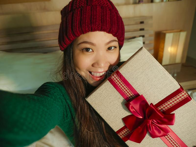 Young beautiful and happy Asian American woman taking selfie picture with mobile phone holding Christmas gift box smiling cheerful stock photo