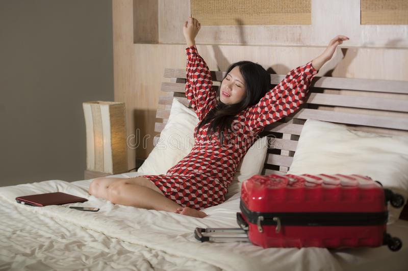 Young beautiful and happy Asian Chinese business woman check in luxury hotel room relaxed and cheerful in elegant chic dress stock photo