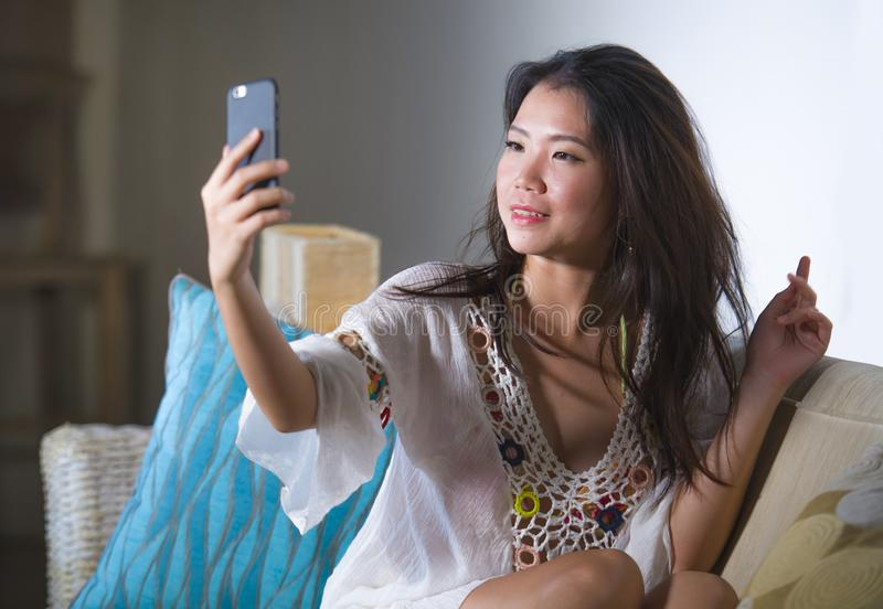 Young beautiful and happy Asian Chinese 20s or 30s woman taking selfie picture with mobile phone sitting at home living room sofa royalty free stock photos