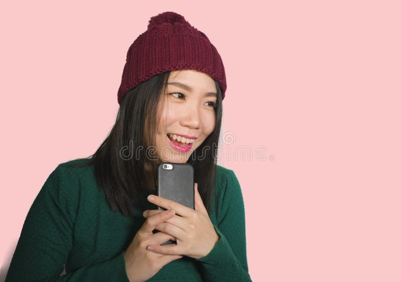Young beautiful and happy Asian Chinese student woman using social media app on mobile phone enjoying excited and playful smiling royalty free stock photos