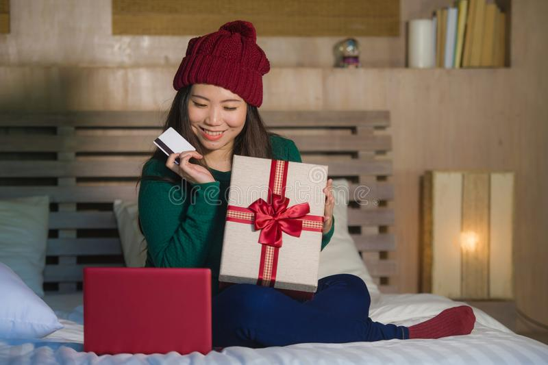 Young beautiful and happy Asian Chinese woman holding credit card and Christmas gift box shopping online xmas presents at home bed royalty free stock image
