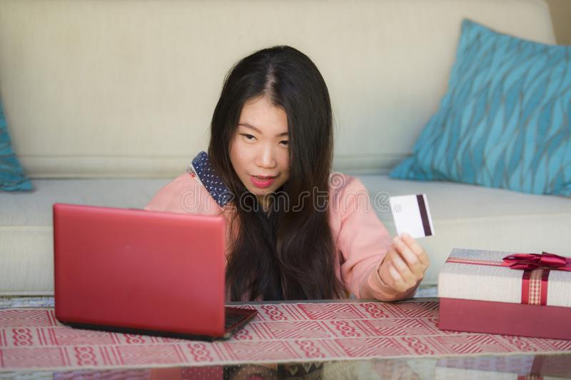 Young beautiful and happy Asian Chinese woman in winter sweater holding credit card and Christmas present box using laptop for int. Young beautiful and happy stock images
