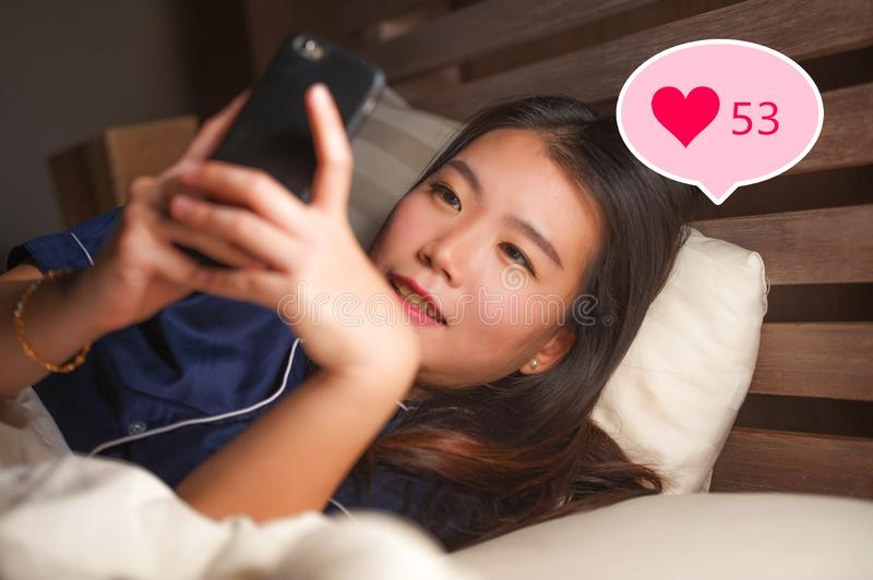 Young beautiful and happy Asian girl getting social media likes. Gorgeous Chinese woman in bed at night excited getting positive. Feedback on internet  app royalty free stock images