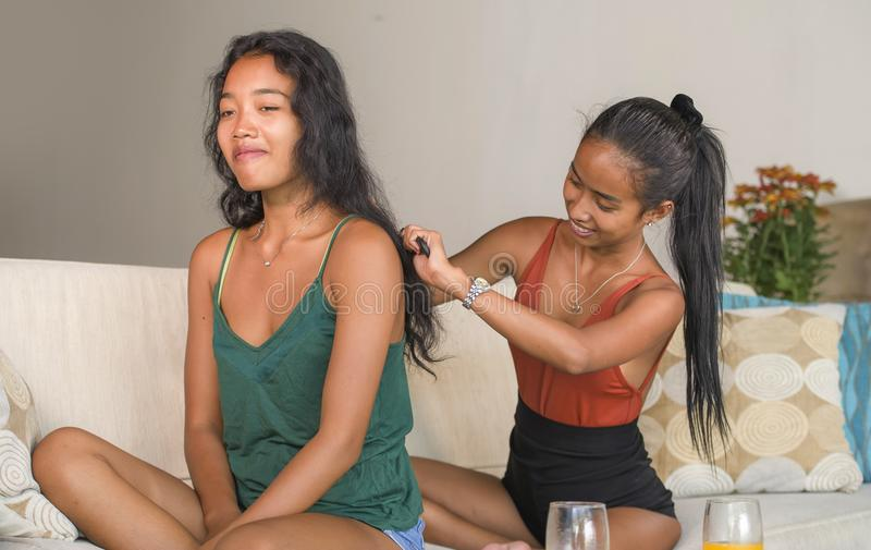 Young beautiful and happy Asian girlfriends at home couch with one girl brushing the hair of the other woman helping preparing for. Young beautiful and happy royalty free stock photos