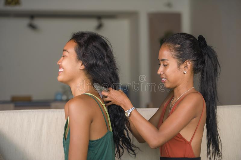 Young beautiful and happy Asian girlfriends at home couch with one girl brushing the hair of the other woman helping preparing for. Young beautiful and happy stock photo