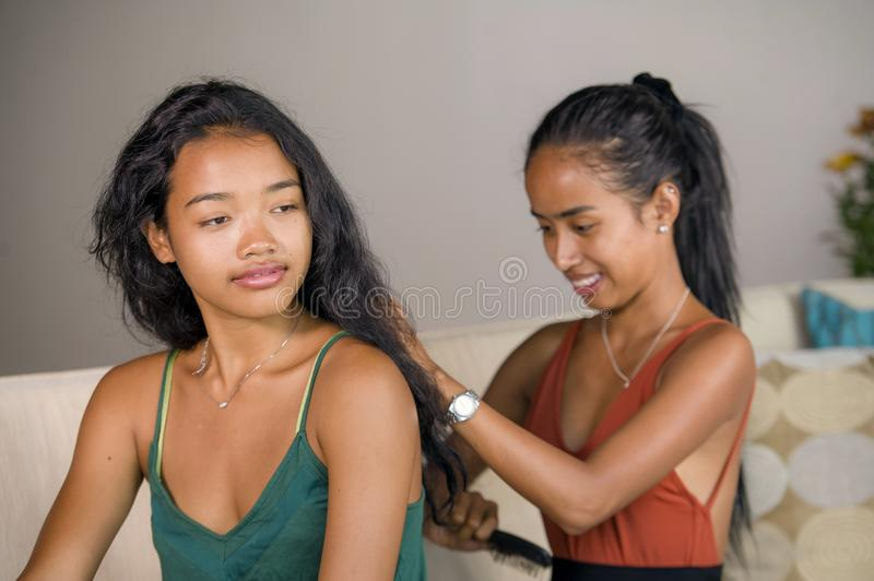 Young beautiful and happy Asian girlfriends at home couch with one girl brushing the hair of the other woman. Young beautiful and happy Asian girlfriends at home stock image