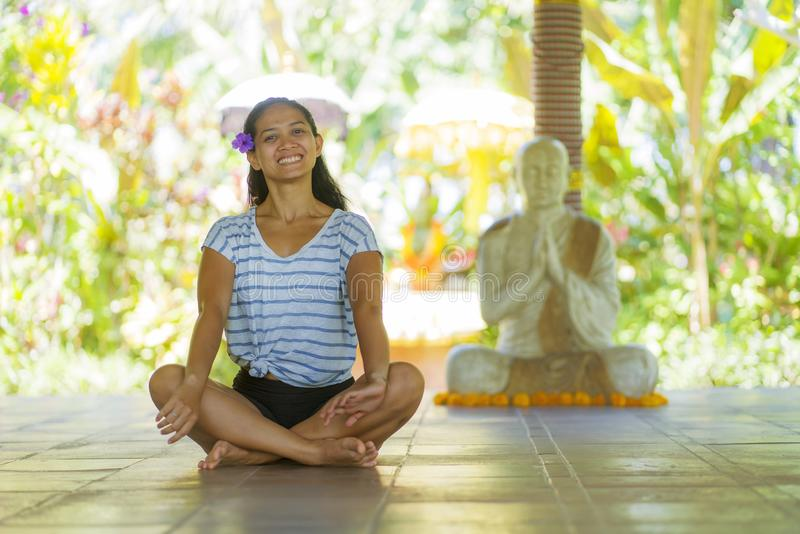 Young beautiful and happy Asian Indonesian woman with Balinese style ear flower sitting on wood floor in lotus pose smiling at. Yoga studio relaxed and zen like royalty free stock photo