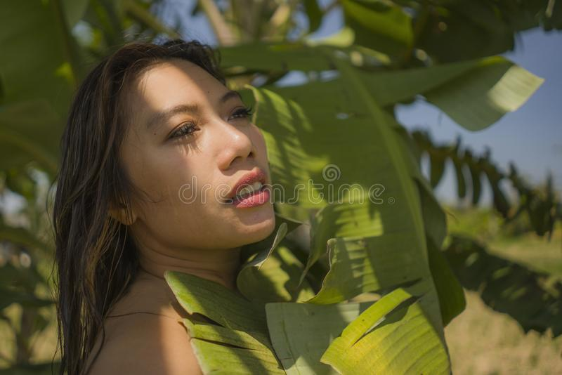Young beautiful and happy Asian Indonesian woman in bikini posing between leaves of banana tree smiling natural isolated on exotic stock photos