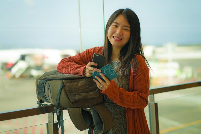 Young beautiful and happy Asian Japanese woman checking mobile phone holding passport at airport departure lounge carrying stock image