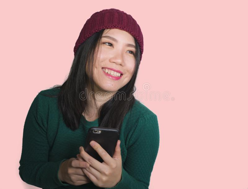 Young beautiful and happy Asian Korean student woman using social media app on mobile phone enjoying excited and playful smiling royalty free stock photography