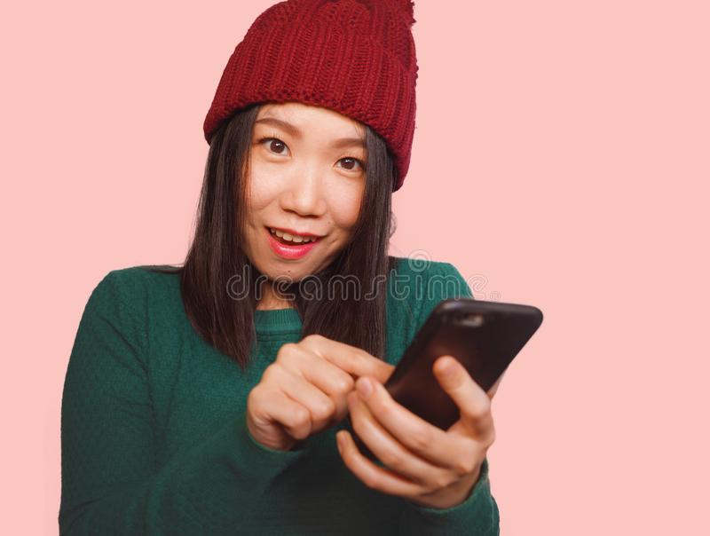 Young beautiful and happy Asian Korean student woman using social media app on mobile phone enjoying excited and playful smiling royalty free stock images