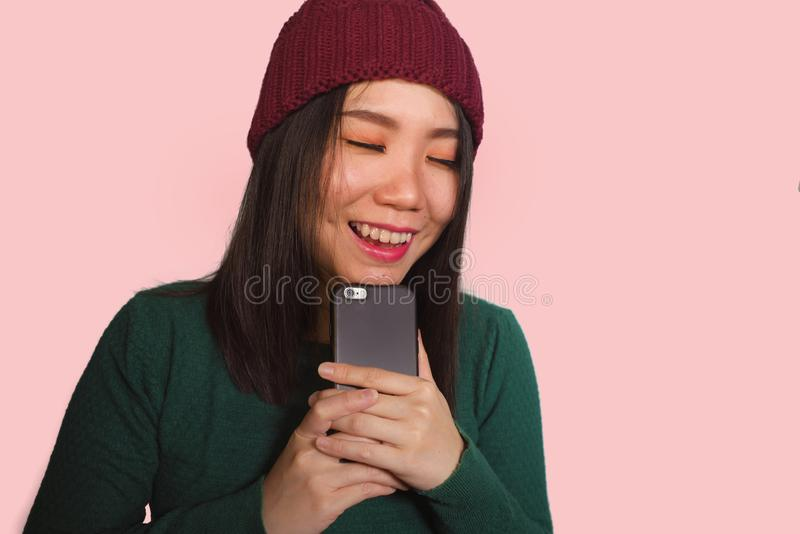 Young beautiful and happy Asian Korean student woman using social media app on mobile phone enjoying excited and playful smiling stock photo