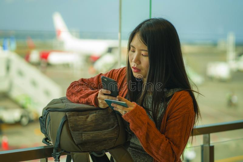 Young beautiful and happy Asian Korean woman checking mobile phone holding passport in her hand at airport departure lounge royalty free stock photos