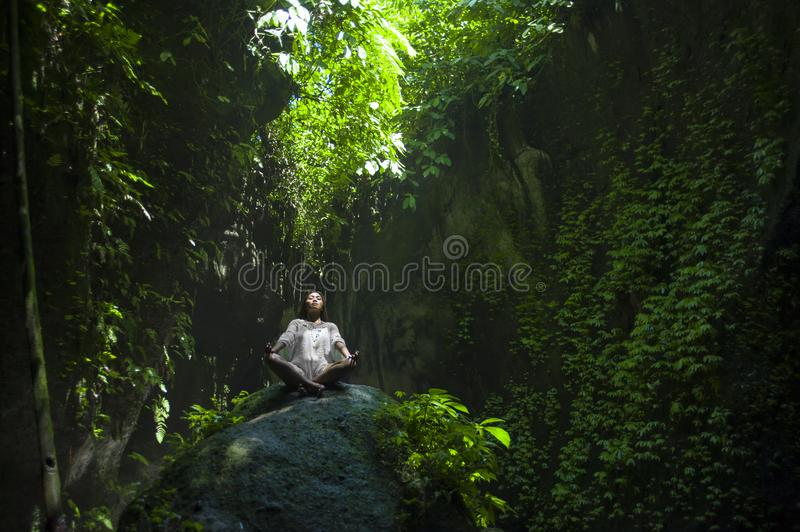 Young beautiful and happy Asian practicing yoga outdoors at amazing peaceful and fresh tropical background sitting in rock doing r stock photos