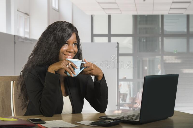 Young beautiful and happy black African American business woman working at office computer desk drinking coffee smiling cheerful stock photos