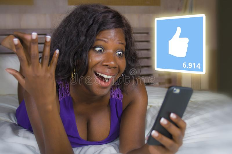 Young beautiful and happy black African American woman in pajamas using mobile phone social media excited and cheerful lying on royalty free stock images