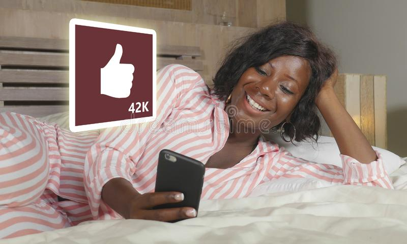Happy black African American woman in pajamas using mobile phone social media smiling cheerful lying on bed at home receiving royalty free stock photos