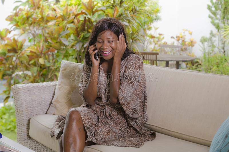 Young beautiful and happy black African American woman talking on mobile phone cheerful and relaxed sitting at sofa couch in hotel. Resort or luxury villa stock photography