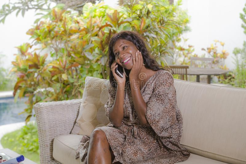 Young beautiful and happy black African American woman talking on mobile phone cheerful and relaxed sitting at sofa couch in hotel. Resort or luxury villa royalty free stock images