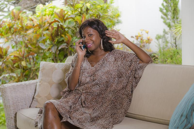 Young beautiful and happy black African American woman talking on mobile phone cheerful and relaxed sitting at sofa couch in hotel. Resort or luxury villa royalty free stock photography