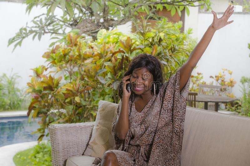 Young beautiful and happy black African American woman talking on mobile phone cheerful and relaxed sitting at sofa couch in hotel. Resort or luxury villa stock image