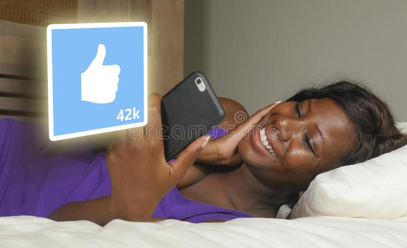 Young beautiful and happy black African American woman using mobile phone social media smiling cheerful lying on bed at home stock images