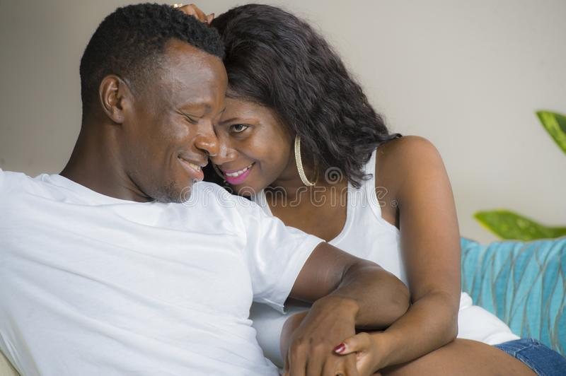 Young beautiful and happy black afro American couple in love relaxed at home living room sofa couch smiling cheerful having fun. Relaxed and cozy in successful stock images