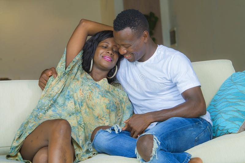 Young beautiful and happy black afro American couple in love relaxed at home living room sofa couch smiling cheerful having fun. Relaxed and cozy in successful royalty free stock photography