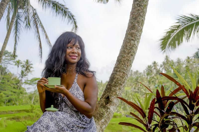Young beautiful and happy black afro American tourist woman drinking coffee or tea visiting jungle plantation in Thailand or Vietn. Am Asia crop fields smiling stock photos