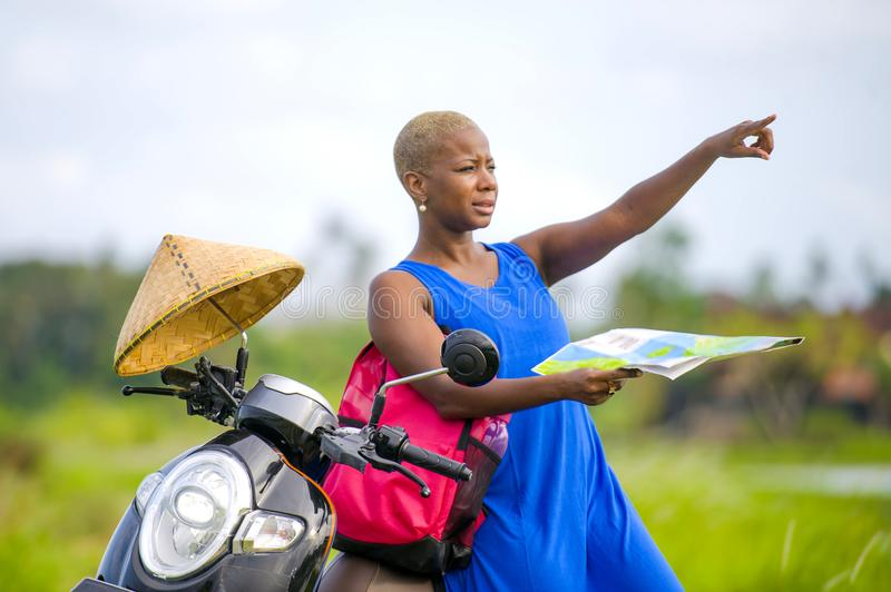 Young beautiful and happy black afro american tourist woman with scooter motorbike looking to road map searching destination explo. Ring fields in Asia holidays stock photography