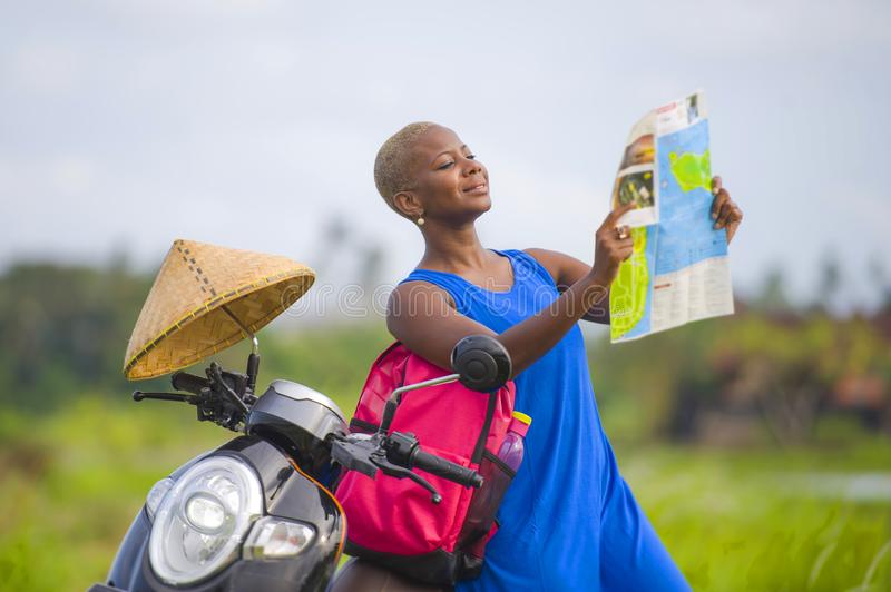 Young beautiful and happy black afro american tourist woman with scooter motorbike looking to road map searching destination explo. Ring fields in Asia holidays stock photos