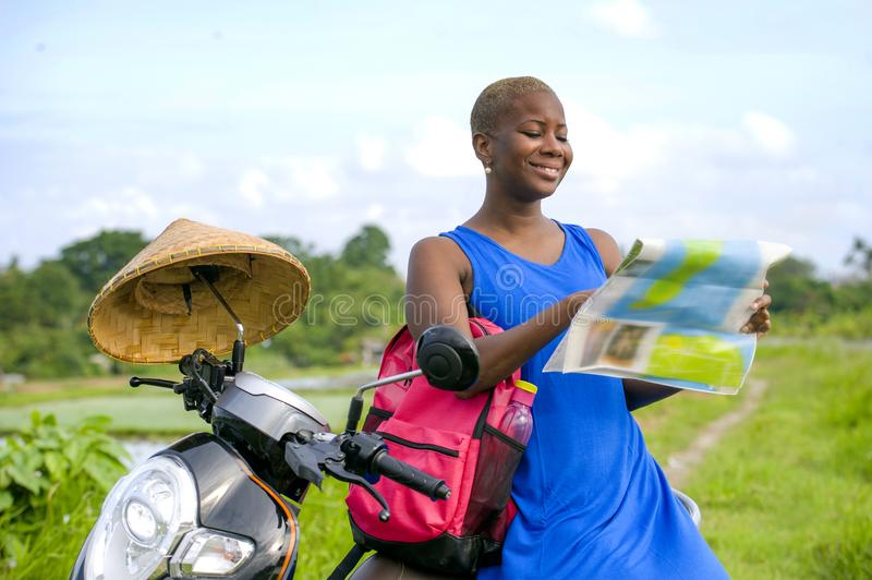 Young beautiful and happy black afro american tourist woman with scooter motorbike looking to road map searching destination explo. Ring fields in Asia holidays royalty free stock images