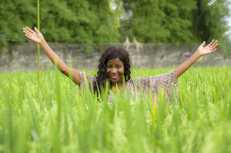 Young beautiful and happy black afro American woman in cool dress having fun at tropical rice field enjoying exotic holidays trip. Outdoors fresh portrait of royalty free stock photos