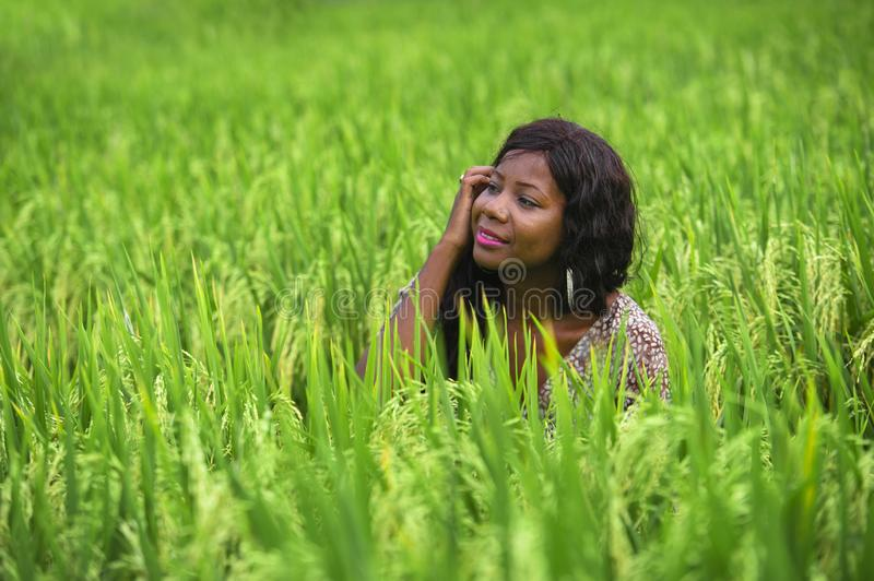 Young beautiful and happy black afro American woman in cool dress having fun at tropical rice field enjoying exotic holidays trip. Outdoors fresh portrait of stock image