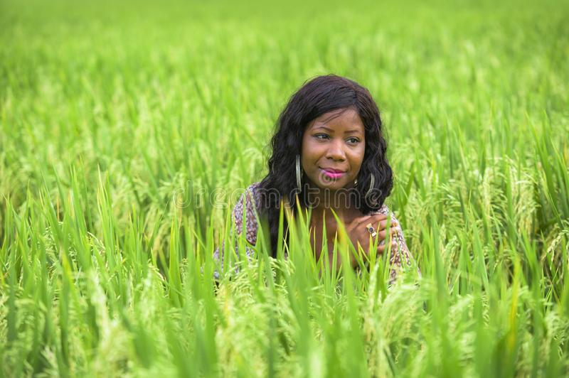 Young beautiful and happy black afro American woman in cool dress having fun at tropical rice field enjoying exotic holidays trip. Outdoors fresh portrait of royalty free stock images