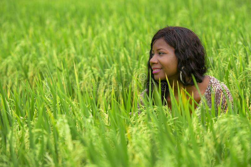 Young beautiful and happy black afro American woman in cool dress having fun at tropical rice field enjoying exotic holidays trip. Outdoors fresh portrait of royalty free stock photography