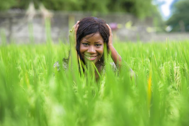 Young beautiful and happy black afro American woman in cool dress having fun at tropical rice field enjoying exotic holidays trip. Outdoors fresh portrait of stock photo