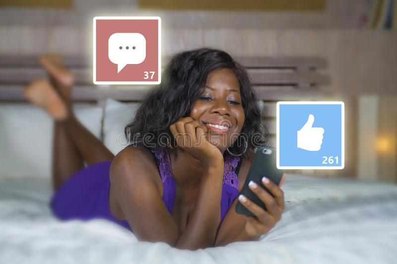 Beautiful and happy black afro American woman in pajamas using mobile phone social media smiling cheerful lying on bed at home royalty free stock photos