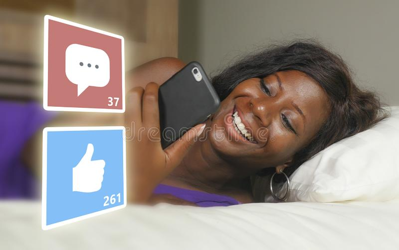 Beautiful and happy black afro American woman in pajamas using mobile phone social media smiling cheerful lying on bed at home royalty free stock images