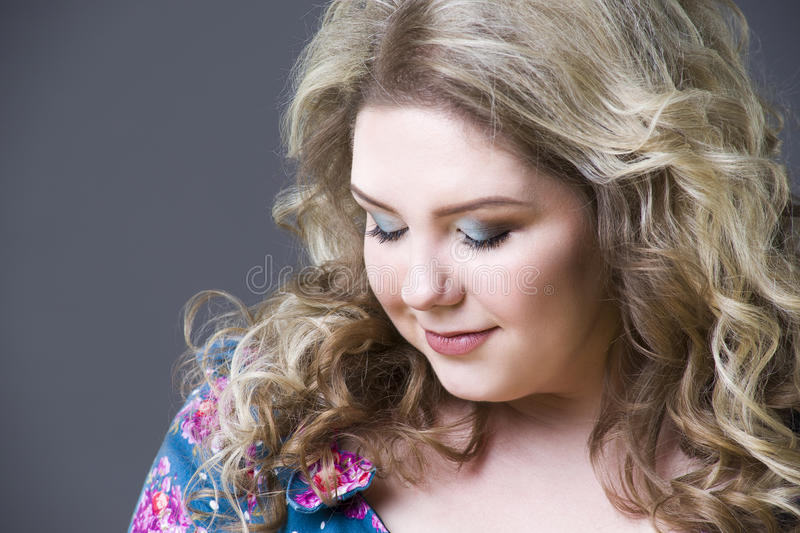 Young beautiful happy blonde plus size model in dres, xxl woman portrait on gray studio background stock photography