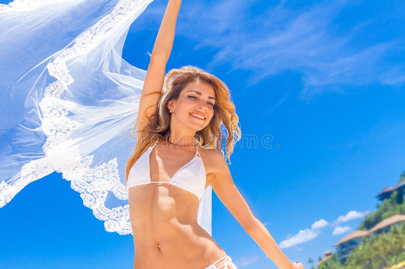 Young beautiful happy bride in white bikini holding flower bouquet on tropical sky and beach background royalty free stock image