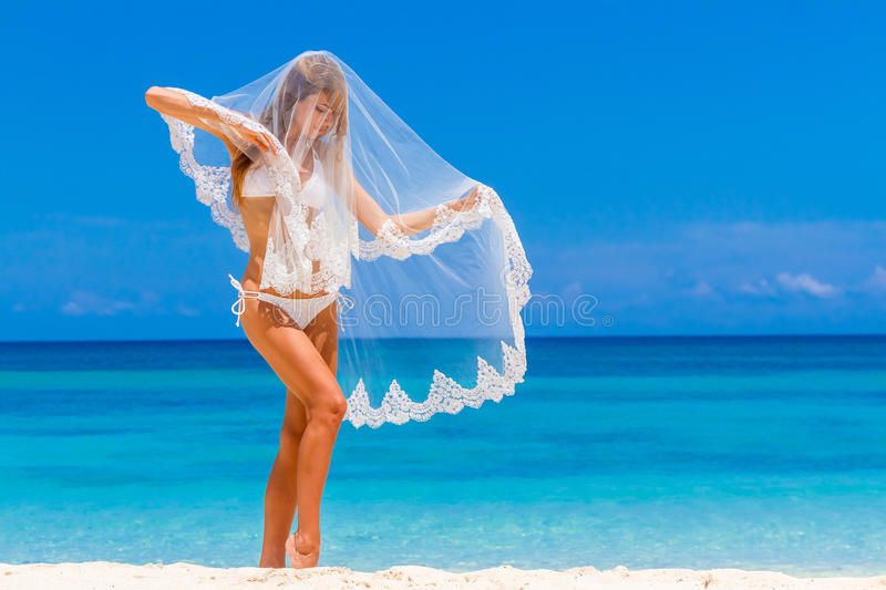 Young beautiful happy bride in white bikini holding flower bouquet on tropical sky and beach background royalty free stock images