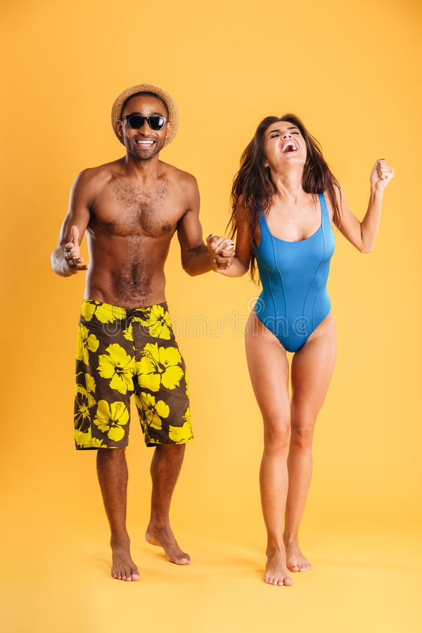 Young beautiful happy cheerful couple in beachwear holding hands stock photos