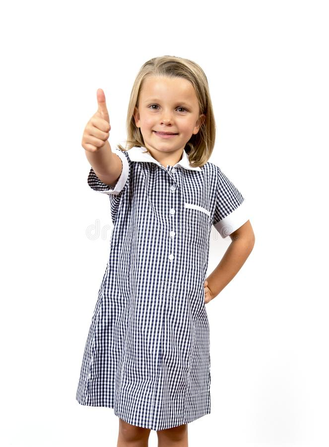 Young beautiful and happy child girl 6 to 8 years old blond hair and blue eyes smiling excited wearing school uniform isolated on. White background in kid royalty free stock photos