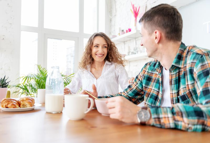 Young beautiful happy couple having breakfast together in the kitchen and chatting stock photo