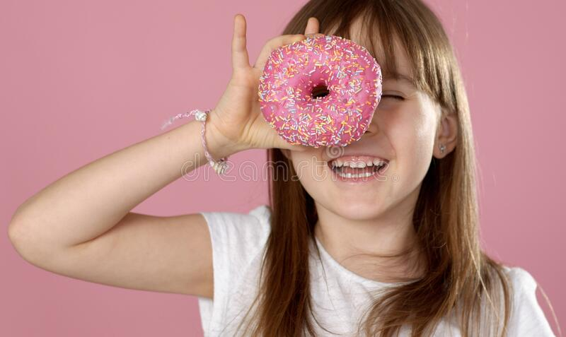 Young beautiful happy and excited blond girl 6 or 7 years old holding donut on her eyes. Looking through. Playing cheerful with cute smile while posing over royalty free stock photo