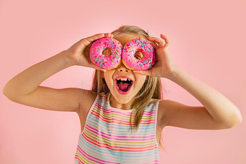 Young beautiful happy and excited blond girl 8 or 9 years old holding two donuts on her eyes looking through them playing cheerful stock photos